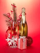 Bouteille de champagne, verres à vin, cadeaux, branche de sapin avec des guirlandes sur fond rouge — Photo