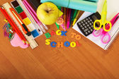 A roll of exercise books, a set for the letter and drawing, a calculator scissors and apple on a table — Stock Photo