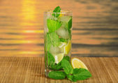 Glass with a mojito, a juicy lime and a spearmint leaf, on a bamboo cloth against the sunset — Stock Photo