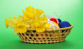 Flowers and eggs with ribbons in a wattled basket, on a green background — Stock Photo