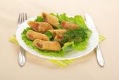 Pannenkoeken met zalm en salade, bestek, kleurrijke servet op gele tafellaken — Stockfoto