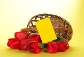 Die roten tulpen, die aus einem korb und leere karte für den buchstaben auf gelbem grund gesunken — Stockfoto