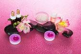 Sada vonných olejů, sůl, svíčky, kameny, květiny, na růžovém pozadí — Stock fotografie