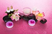 Set of fragrant oils, salt, candles, stones, a flower, on a pink background — Stock Photo