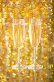 Two glasses of champagne, on an indistinct gold background — Stock Photo