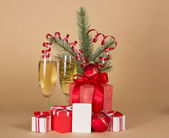 Christmas gifts, toys, tinsel, fir-tree branch, champagne and empty card, on a beige background — Stock Photo