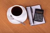 Αδειάστε φύλλα για σημειώσεις, τη λαβή ο υπολογιστής και ένα φλιτζάνι καφέ σε έναν πίνακα — Φωτογραφία Αρχείου