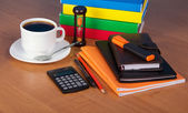 Notepad, exercise book, organizer, marker, books, the calculator, hourglasses and a cup of coffee on a table — Stock Photo