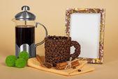Taza de café, la copa, un marco, palitos de canela, crisantemo verde y servilleta sobre el beige — Foto de Stock