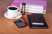 Notepad, organizer, pencil and pen, folders for documents the calculator, hourglasses and a cup of coffee on a table — Stock Photo