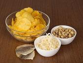 Chips, pistachos, calamares secos y pescado salado, sobre una mesa — Foto de Stock