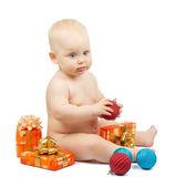 Bebê fofo detém a bola vermelha, caixa de presente de Natal, bolas coloridas de vermelhas e azuis isoladas no branco — Fotografia Stock