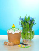Easter cake, sweet jewelry, cinnamon, vanilla, vase with the flowers on a table, on a blue background — Stock Photo