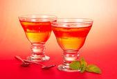 Dos copas de la fruta de la jalea, dos cucharaditas, hoja de menta verde sobre un fondo rosa — Foto de Stock