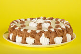 Maravillosa tarta en un plato sobre un fondo amarillo — Foto de Stock