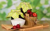 Frascos de mermelada, cubo con fresa con azúcar una taza y una cuchara con bayas, servilletas en una mesa — Foto de Stock