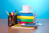 Books, exercise books, office accessories in a support, a hourglass a cup of coffee on a table — Stock Photo