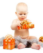 Cute baby develops christmas gift box with silver tinsel isolated on white — Stock Photo