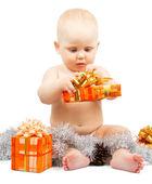 Roztomilé dítě rozvíjí Vánoční dárková krabička s stříbrným pozlátko izolovaných na bílém — Stock fotografie