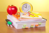 The book, exercise books, a marker scissors a pens an alarm clock and apple on a yellow background — Stock Photo