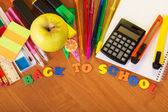 Blank exercise book sheets, handles, markers, the calculator a cutter and apple on a table — Stock Photo