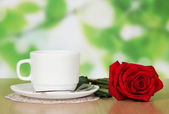 Cup of coffee with a red rose — Stock Photo