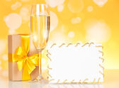 Champagne glass, gift and empty card — Stock Photo