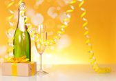 Champagne, glass, gift and serpentine — Stock Photo