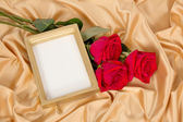 Empty photoframe with a bouquet of red roses — Photo