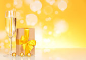 Glass with champagne and a gift — Stock Photo