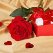 Red roses and gift box on golden fabric — Stock Photo
