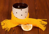 Сup of hot tea with lemon wrapped in yellow scarf — Stock Photo