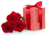 Dárek a tři červené růže blízko — Stock fotografie