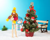 Wooden man holding a Christmas gift — Stock Photo