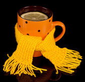 Cup of tea with lemon tied a yellow scarf — Stock Photo