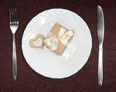 Gift box with red heart on plate — Stock Photo