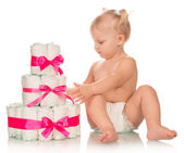 Baby girl with heap of diapers — Stock Photo