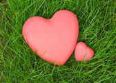 Red hearts on green grass — Stock Photo