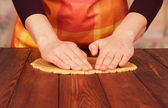 Women's hands knead the dough — Stock Photo