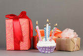 Cupcakes with candles and gift boxes — Stock Photo