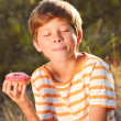 Young boy eating donut outdoors — Stock Photo