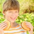 Smiling child holding two burgers — Stock Photo