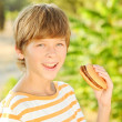 Child eating hamburger outdoors — Stock Photo
