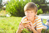 Child lying on grass eating burger — Stock Photo