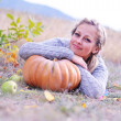 Smiling woman with pumpkin outdoors — Stock Photo