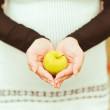 Green apple in woman hands — Stock Photo