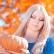 Woman holding pumpkin outdoors — Stock Photo