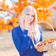Girl with basket full of apples outdoors — Stock Photo
