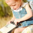 Little girl reading book outdoors — Stock Photo