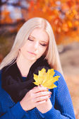 Woman with closed eyes and yellow leaf outdoors — Stock Photo